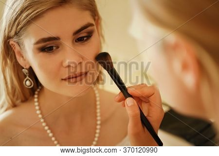 Make-up Artist Makes Professional Makeup Of A Young Woman, A Bride. The Bride In A White Dress, A Pe