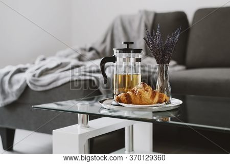 Fresh Croissant And French Press Pot With Brewed Herbal Tea And Vase With Dried Lavender On Glass Co