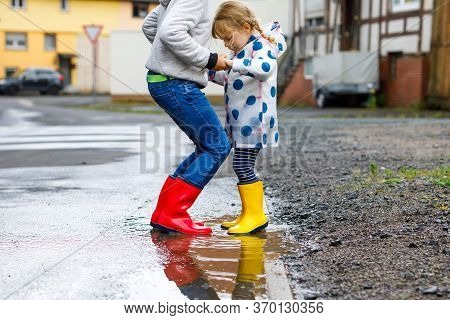 Close-up Of Two Children, Toddler Girl And Kid Boy Wearing Red And Yellow Rain Boots, Walking During