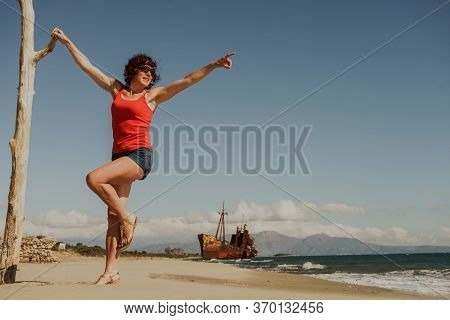 Travel Freedom. Mature Tourist Woman On Beach Enjoying Summer Vacation. An Old Abandoned Shipwreck,