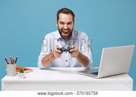 Laughing Young Bearded Man In Light Shirt Sit Work At White Desk With Pc Laptop Isolated On Pastel B