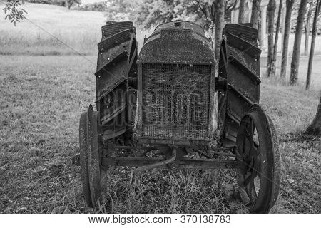 Closeup Of An Old Rusty Tractor Disused And Abandoned Among The Trees In The Meadows Of The Bregonze