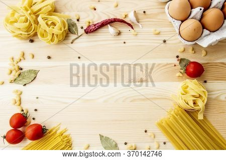 Cooking Food Background With Free Space For Text. Composition With Pasta, Tomato, Eggs, Garlic, Bay