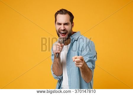 Cheerful Young Man In Casual Blue Shirt Posing Isolated On Yellow Orange Background In Studio. Peopl