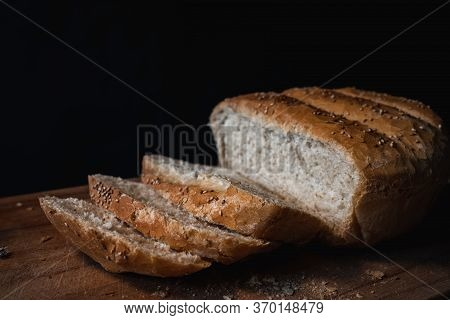 Home Made And Baked Grain Bread On A Wooden Table With Black Background And Copy Space