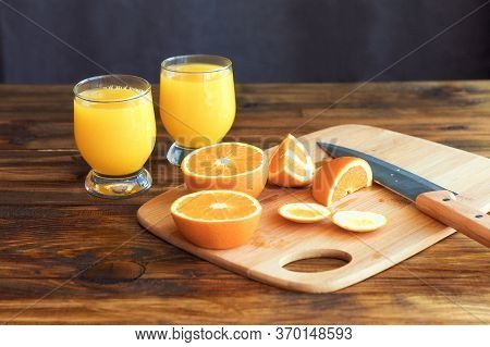 The Process Of Making Orange Juice In The Home Kitchen. A Glass Of Fresh Juice. Oranges On The Table