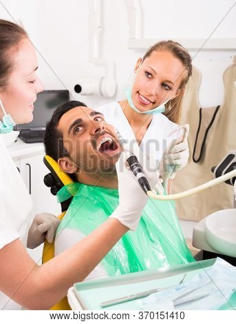 Female Dentist With Assistant Diagnostics The Oral Cavity Of Male Patient At Clinic.