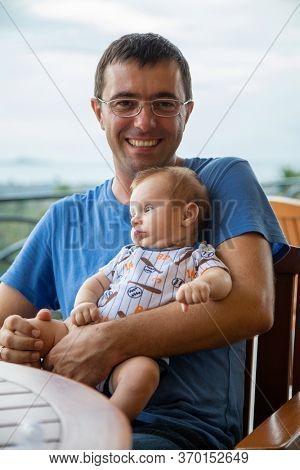 Happy dad holds baby boy