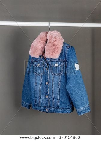 Children's Short Denim Jacket With A Collar Of Pink Faux Fur Hanging On A Hanger Against A Gray Wall