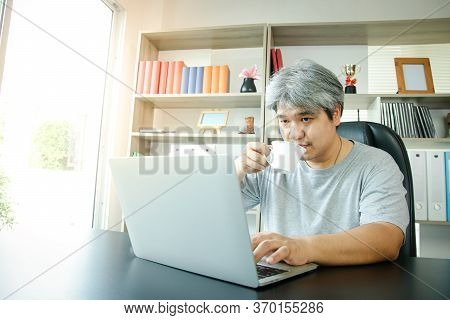 Asian Men Work At Home In The Office. Drinking Coffee And Typing In Computer Notebooks. Entrepreneur