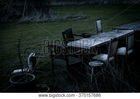 A Table And Some Charis Have Been Left Outside, Giving The Feeling Of Mystery, Abandonment Or Vandal