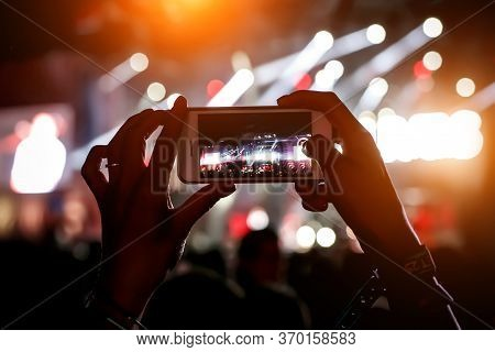 Mobile Phone In Hands At A Music Show. Using A Smartphone Concept.