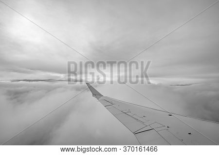 On An Airplane In The Sky Above Clouds