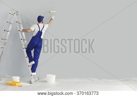 Building Contractor Painting Grey Wall With Roller Brush, Copy Space Text. Construction Worker Renov