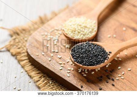 Black And White Sesame Seeds In A Wooden Spoon On Wood Table. White Sesame Helps To Strengthen Bones