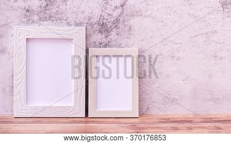 Two Picture Frame On Wall Background And Wooden Table. Poster Product Design Styled