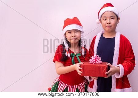 Asian Boy In Santa Clothes And Girl In Elf Clothes Holding Gift. Merry Christmas