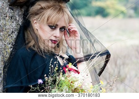 Mysterious Sexy Blonde Woman In A Red Dress And Black Cloak, With A Black Veil On Her Head. In Natur