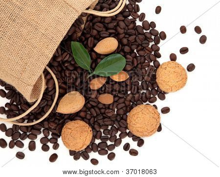 Coffee beans in a hessian drawstring sack and loose with amaretto biscuits, almond nuts and leaf sprigs  over white background.