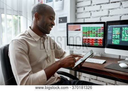 Stylish African Businessman, Trader Sitting By Desk In Front Of Multiple Monitors And Using His Smar