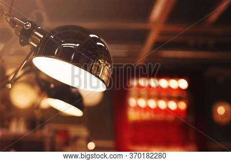 Low Angle Closeup Of Modern Lamp With Mirrored Metal Lampshade Glowing In Illuminated Room With Blur