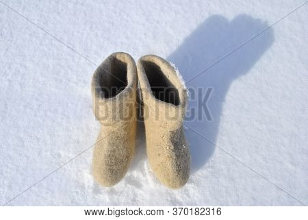 White Boots Stand In The Snow. Boots Top View. Valenoks Are Covered With Small Ice Floes. Snow Stuck
