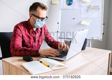 Young Concentrated Man Works In The Office While Pandemic Situation. An Office Worker Sits At The Of