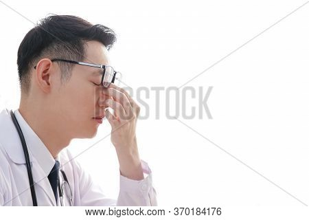 Asian Male Doctors Are Stressed From The Treatment Of Patients, Using Hands To Massage The Nose To H
