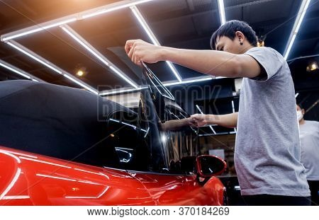 Applying Tinting Foil On A Car Window In A Auto Service