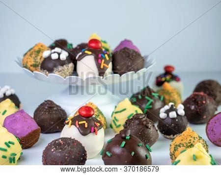 White Raised Platter Filled With A Variety Of Cake Balls With More On The Counter Beneath It.  Banan