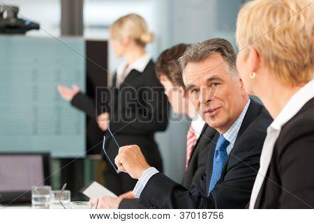 Business - Präsentation innerhalb eines Teams, eines weiblich, Kollege steht auf dem Flipchart, ein Mann ist