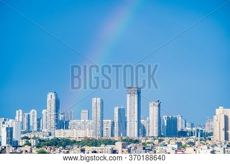 Aerial Cityscape Shot Of Buildings In Gurgaon Delhi Noida With A Rainbow Behind Them On A Monsoon Da