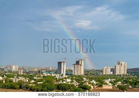 Aerial Cityscape Shot Of Buildings In Gurgaon Delhi Noida With A Rainbow Behind Them On A Monsoon Da