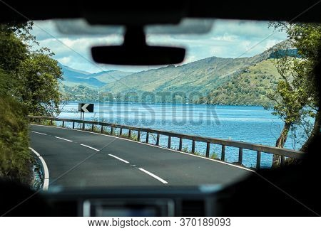 Bendy Roads In The Scottish Mountains Near A Massive Lake From The Perspective Of A Car Passenger.