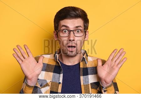 Young Amazed Handsome Man In Glasses Standing On Yellow Wall Raising Arms Wondering, Astonished To S