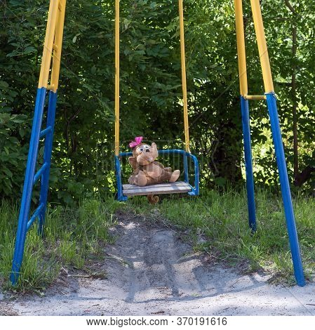 Soft Toy Sits On A Children's Swing On A Summer Sunny Day