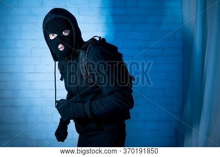 Burglary Concept. Intruder In Black Balaclava Standing In Apartment Or Office In The Dark, Looking A