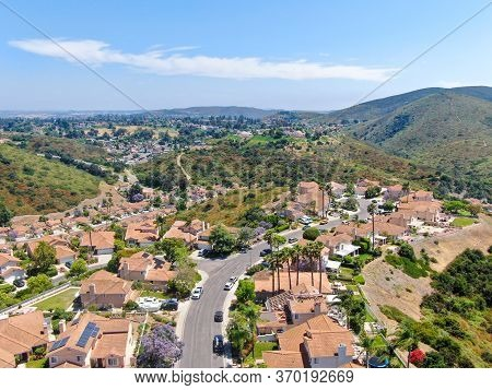 Aerial View Of Middle Class Neighborhood With Residential House With Swimming Pool And Mountain On T