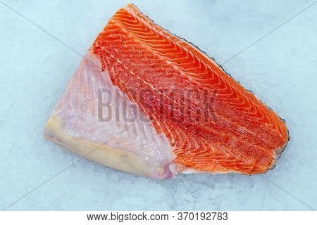 Raw Salmon Meat Is Taken Close-up. Sale Of Fresh Red Fish