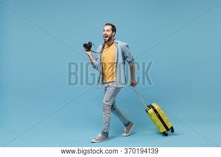 Excited Traveler Tourist Man In Yellow Summer Casual Clothes With Photo Camera Isolated On Blue Back