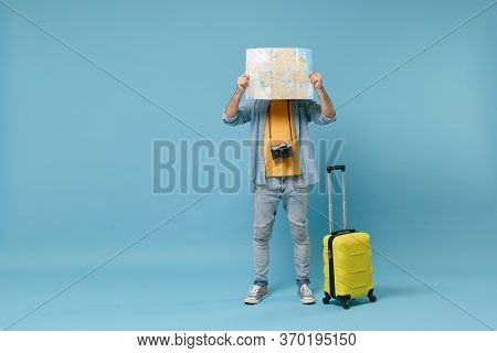 Traveler Tourist Man In Yellow Clothes With Photo Camera, Suitcase Isolated On Blue Background. Male