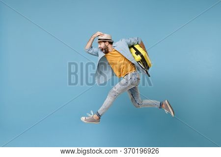 Side View Of Excited Traveler Tourist Man In Yellow Clothes Isolated On Blue Background. Male Passen