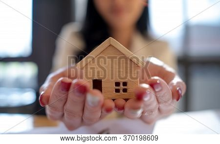 House Selling Holding A Wood Model House In Hands. Concept For Housing And Real Estate Agent Offerin
