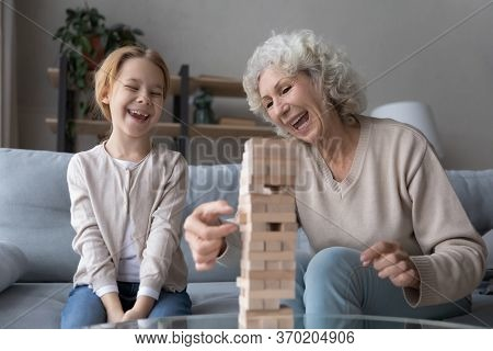 Overjoyed Grandmother And Granddaughter Play Stacking Game