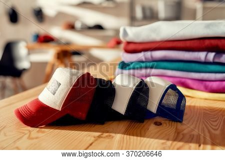 Custom Apparel, Clothes Neatly Folded On Shelves. Stack Of Colorful Clothing And Baseball Caps In Th