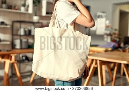 Cropped Shot Of Female Worker Posing With Custom Shopper Bag In The Store. Young Woman Working At Cu