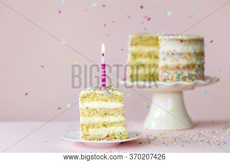 Funfetti birthday layer cake with one candle and a single slice removed against a pink background