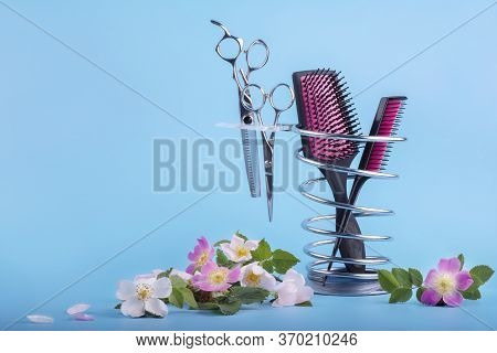 Hairdressing Tools On A Metal Stand Decorated With Delicate Pink Flowers On A Blue Background