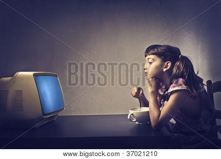 Niño viendo la televisión durante el desayuno