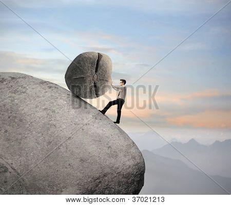 Businessman pushing a boulder on a rock